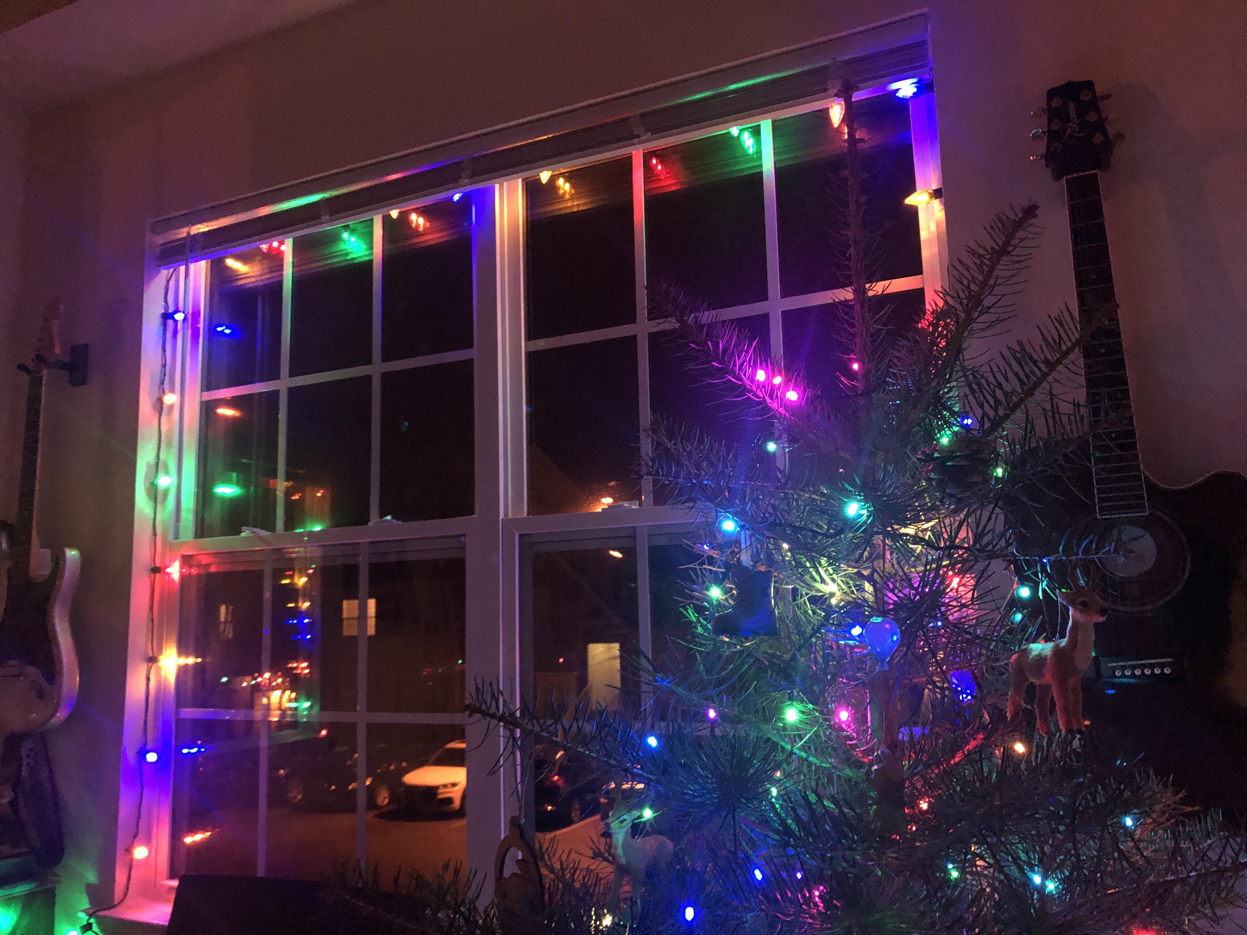 Luces de Navidad en un árbol y alrededor de una ventana.